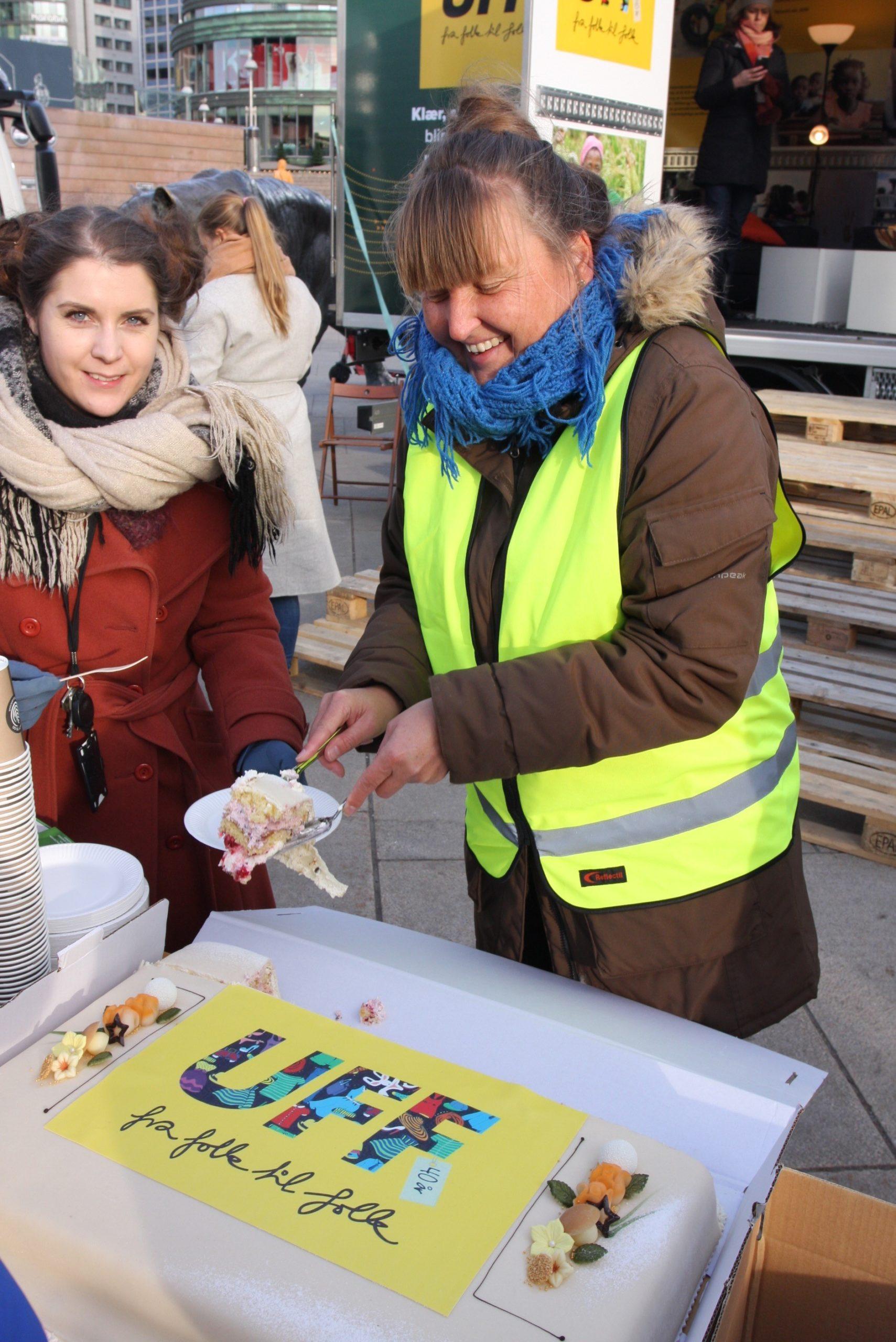 Sara Bjareng, avdelingsleder i UFF Second Hand (t.v.) og informasjonsansvarlig Rosa Fridh i UFF Norge t.h. og serverer jubileumskake til de frammøtte etter seremonien på Jernbanetorget.