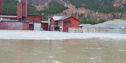 KULER I ELVA: Fabrikkens lagerområde ble oversvømt i oktober 2018 og 25 tonn med skumglasskuler ble ført nedover vassdraget. Foto: Glasopor as.